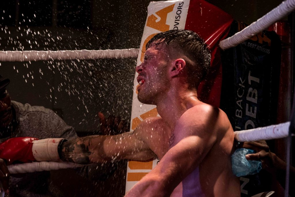 white male boxer being doused with water in the corner